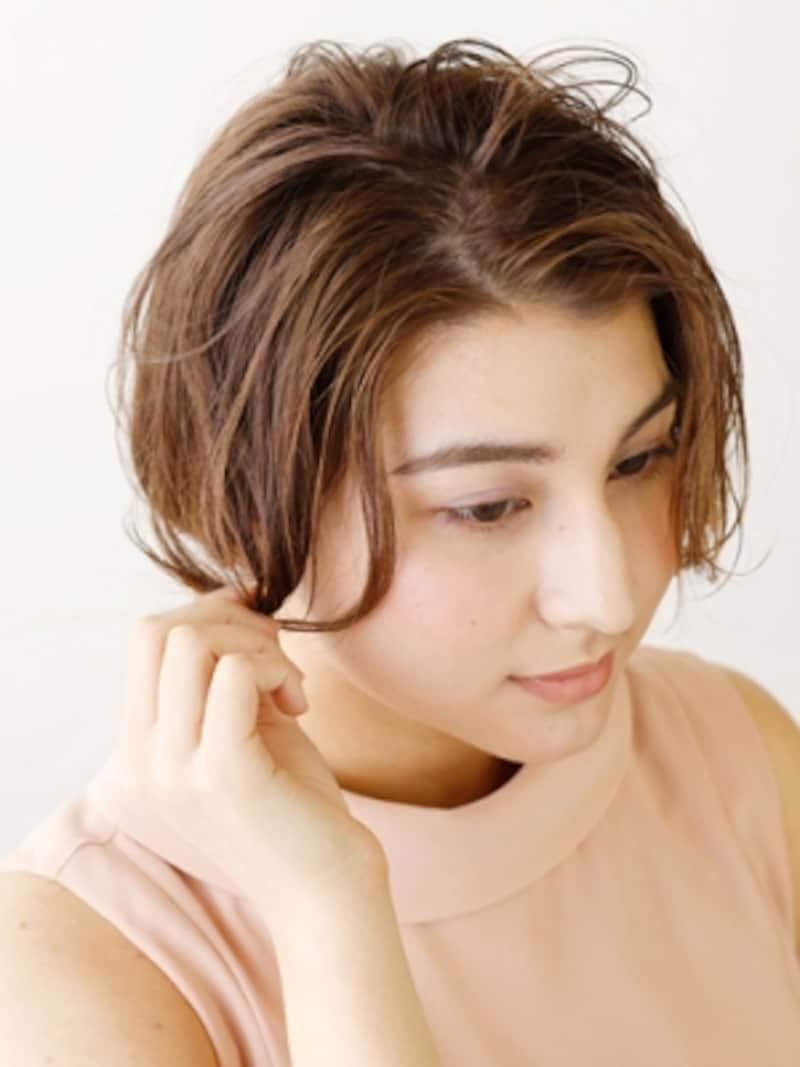 顔まわりの髪を巻き、ほぐしながら毛束を作る