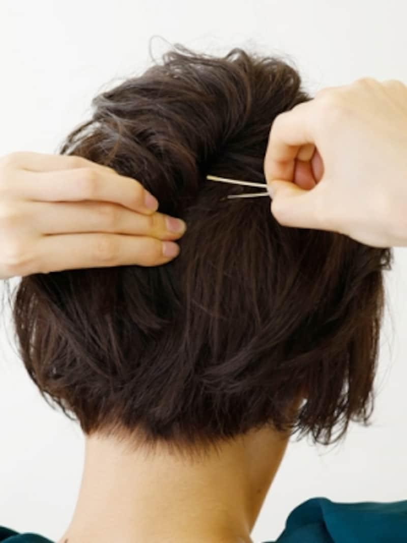 ねじった毛束を少し押し上げながらピンで固定