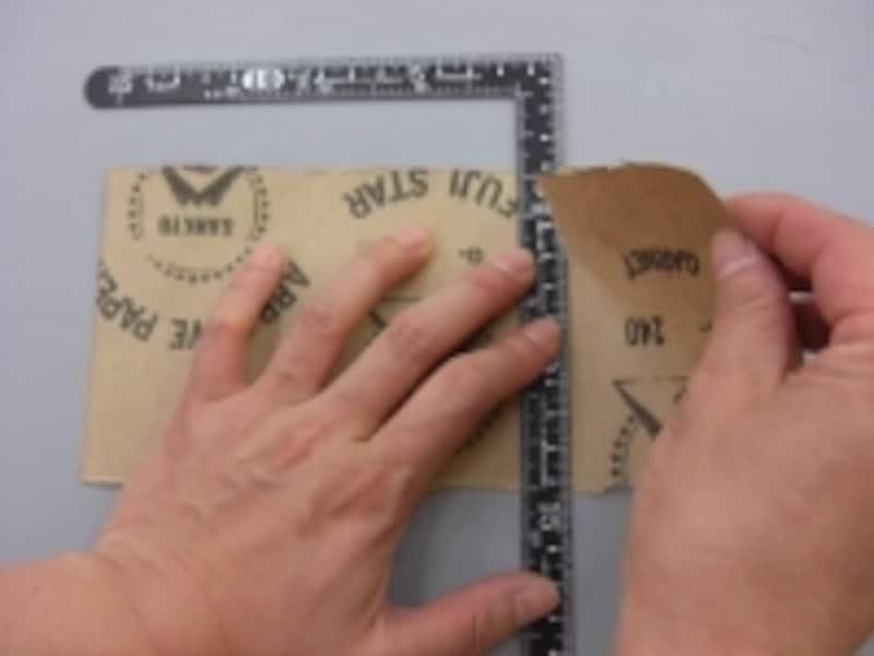 定規をしっかり押さえてサンドペーパーを切ります