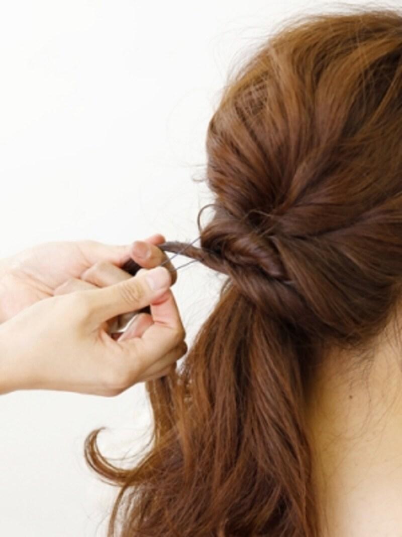 残りの髪を2つに分け、ねじりながらピンで固定