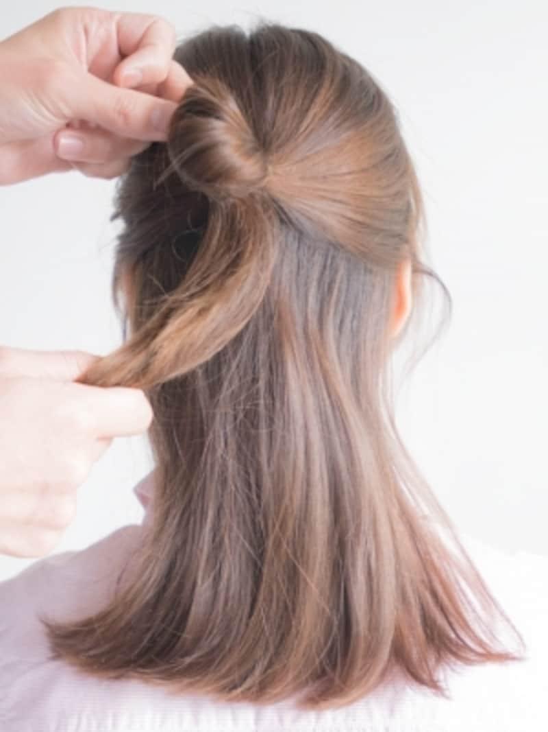 分けとった髪をゴムで結ぶ