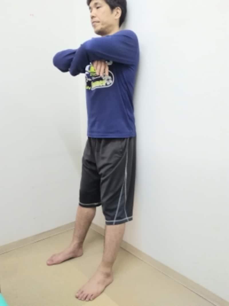 壁に背中をつけて腕を体の前で組みます