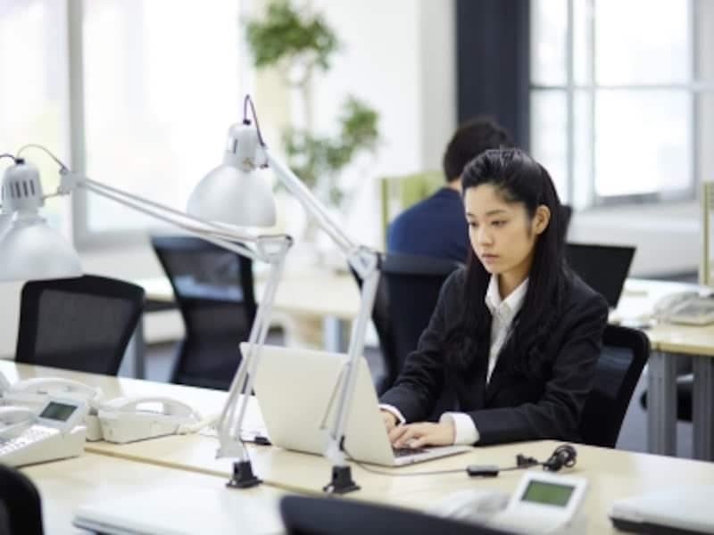 パソコンで作業する無表情の女性