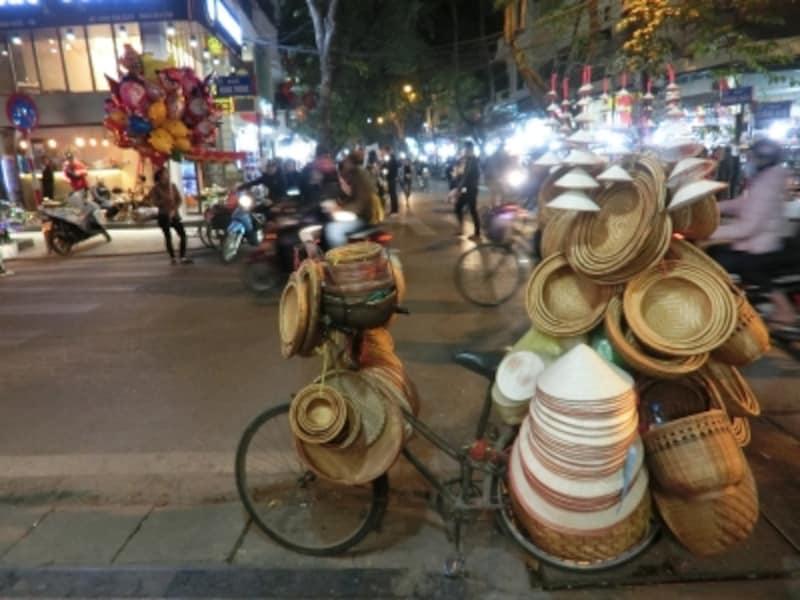 人と、バイクと、喧騒と。人々の生活臭とアジアの熱気あふれるハノイの街角。ノンラーと呼ばれる菅笠はベトナム人の永遠のシンボル