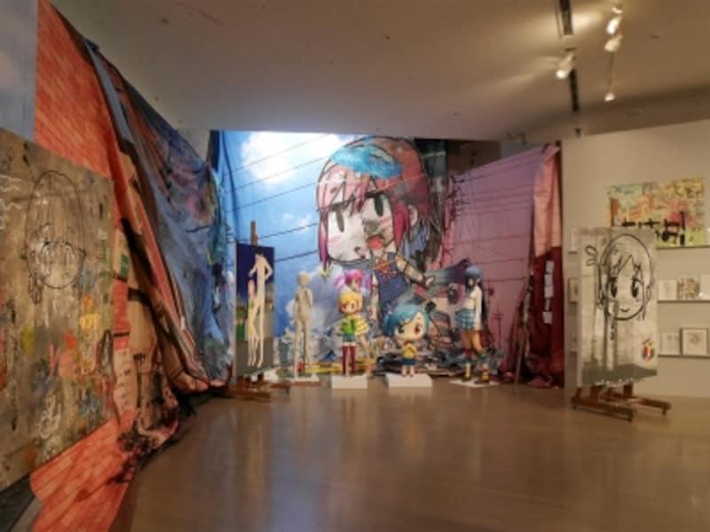 ミスター《「ごめんなさい」展示風景》……アニメやゲームキャラクター風のタッチで描かれる少女像など、日本独自の進化を遂げた「ガラパゴス」的なオタクカルチャーや萌え絵の無垢さを、アートとして奇想に変容した作品が並びます。フィギュアやこれまで公開したことのないドローイングなども展示。ヨコハマトリエンナーレ2017展示風景(2017年8月3日撮影)