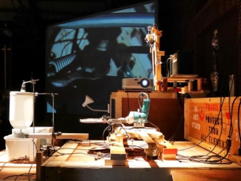 宇治野宗輝《プライウッド新地》2017……美術作品の輸送に使われる大型の木箱をビル群に見立てた作品。そこでは、突如、楽器とミキサーやテレビなどの生活用品を組み合わせた装置が、自動で光と音を発するパフォーマンスを始めます。ヨコハマトリエンナーレ2017展示風景(2017年8月3日撮影)