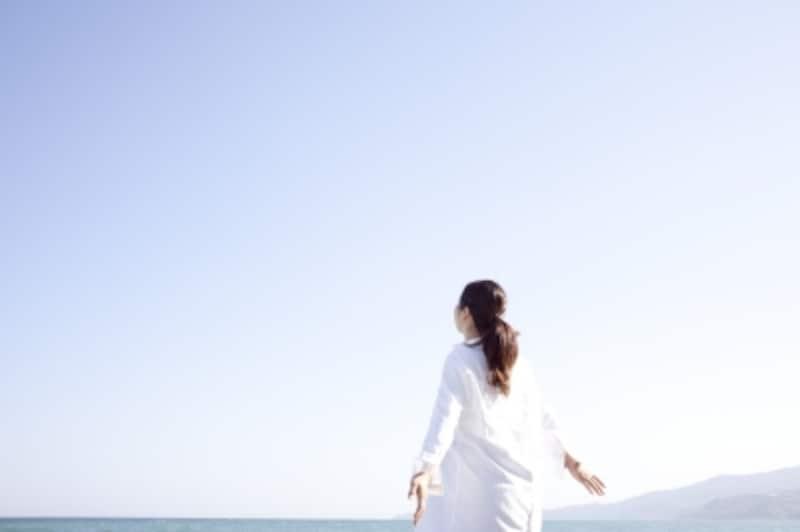 海岸で手を広げて立つ女性