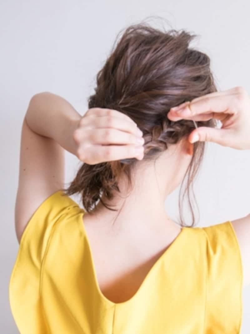 三つ編みの毛先をゴムで結ぶ