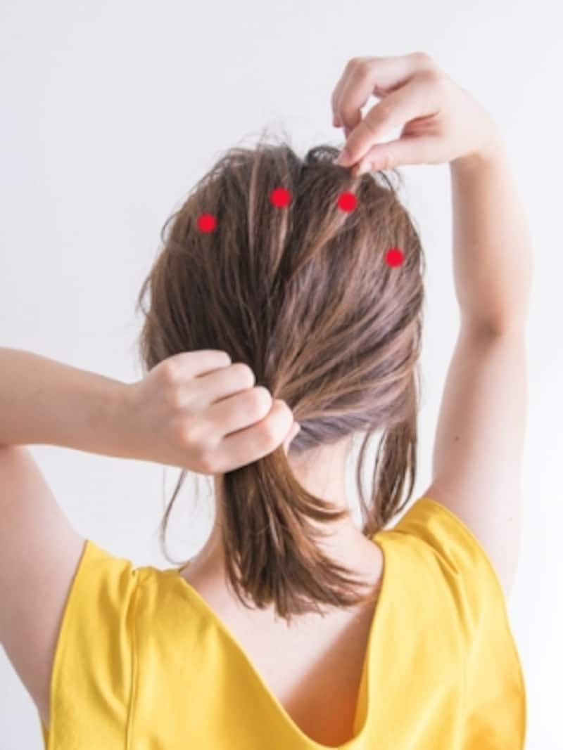 髪をひとつにまとめながらトップの毛束を引き出す