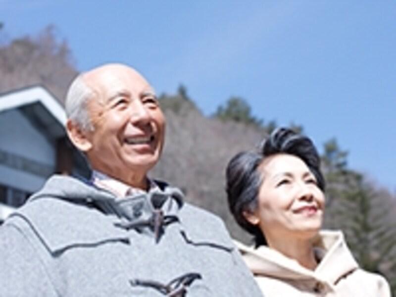 家の前に立つ高齢夫婦