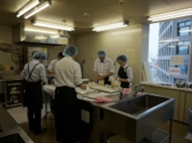 厨房では、調理器具や食器を洗う。講師の指導のもと効率よく作業が進む。