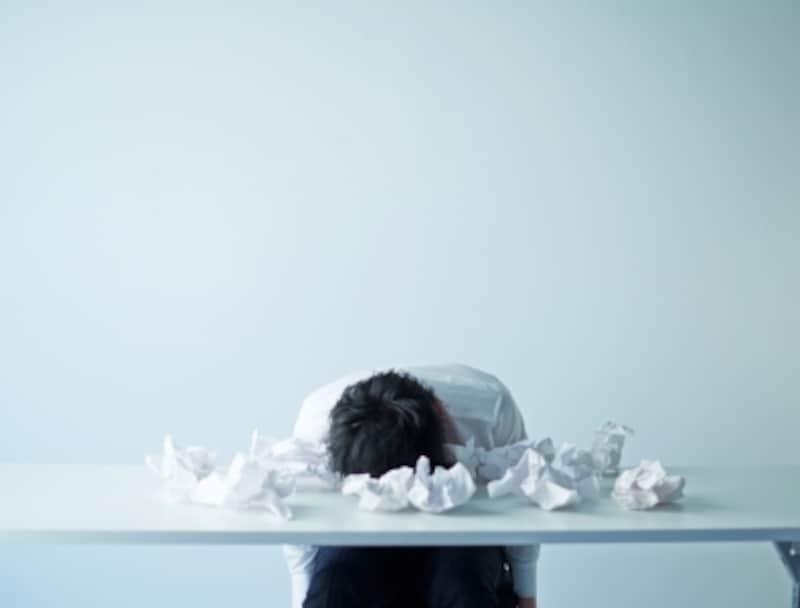 疲れて紙ごみの散乱する机に伏している人