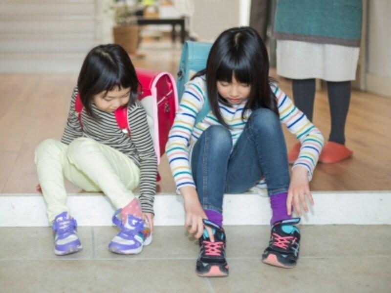 玄関で靴を履く子ども