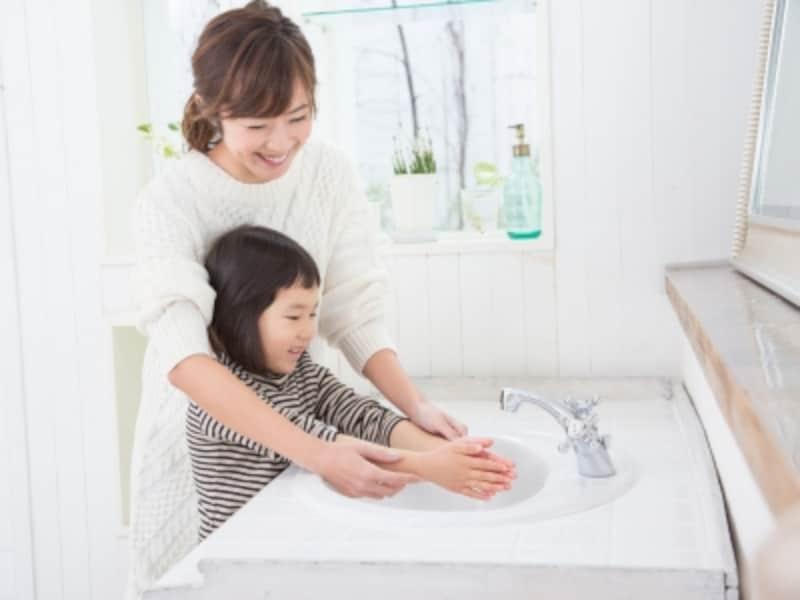 洗面所で手を洗う母と子ども