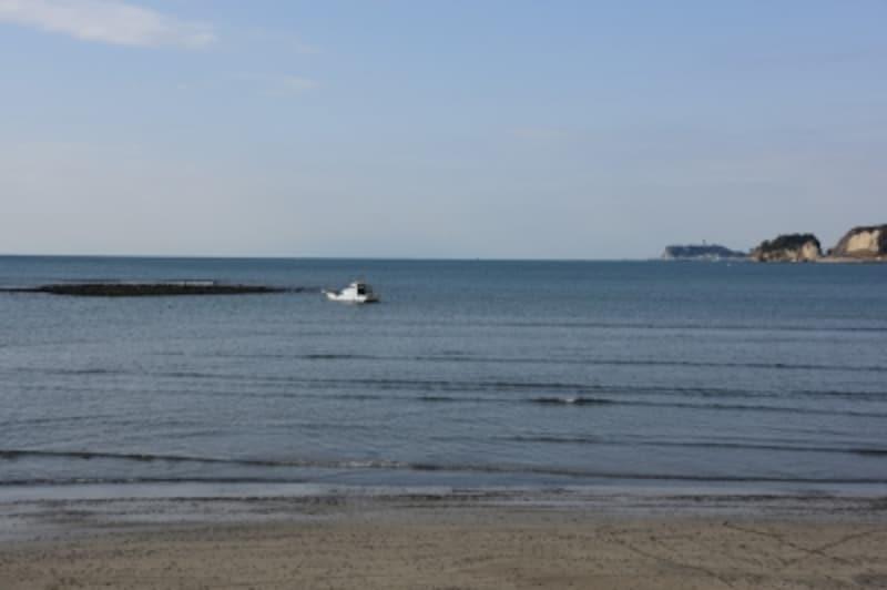 漁船の左に見えるのが、鎌倉沖に浮かぶ人工島「和賀江嶋」