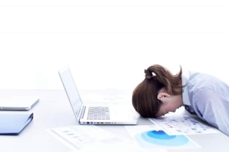 パソコンの前で伏せっている女性
