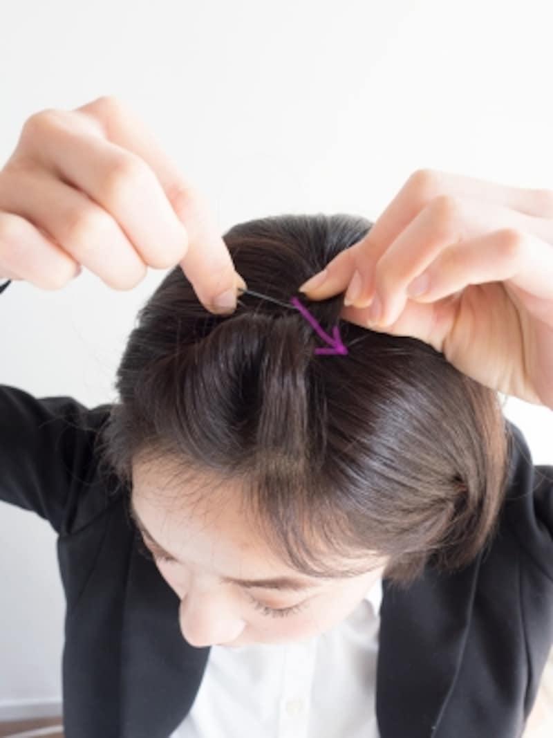 前髪を一回転ねじり、矢印の方向にピンで固定