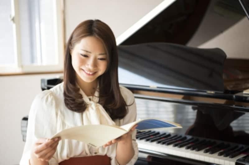 女性がピアノの前で楽譜を見ている写真
