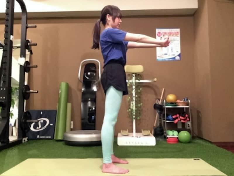 動作1.足を肩幅に開き、両手を前に伸ばします。