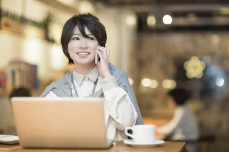 パソコンを見ながら電話をかける女性