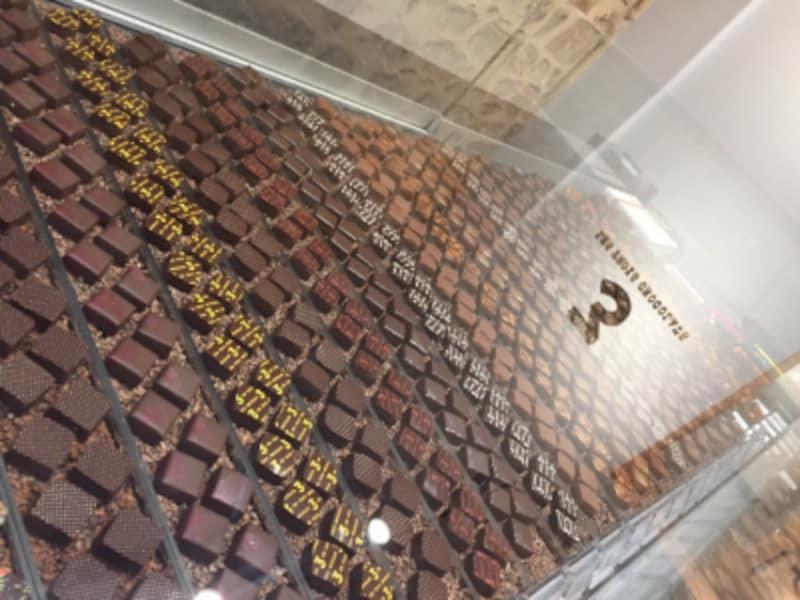 カカオニブが敷き詰められたショーケースに並ぶボンボンショコラ