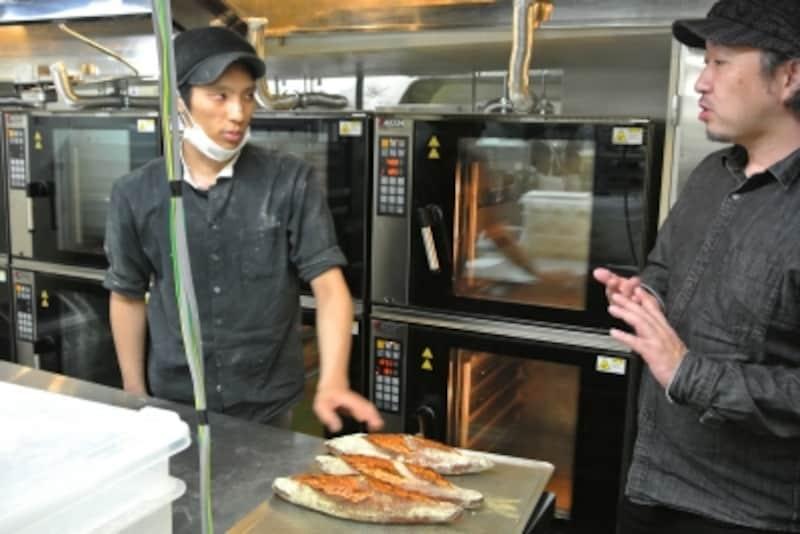 パンをチェックする杉窪さん。厨房にはコンベクションオーブンが並ぶ