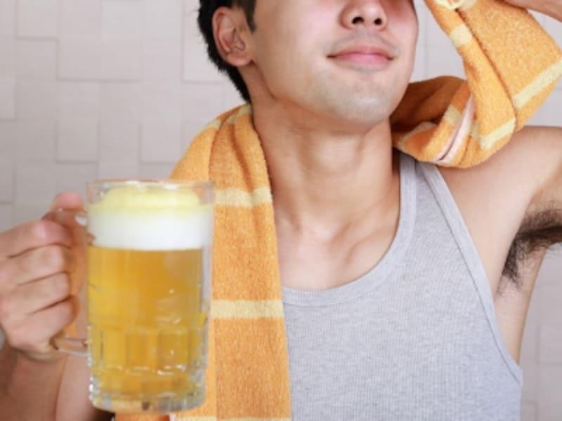 スポーツ後のビールを楽しむ男性