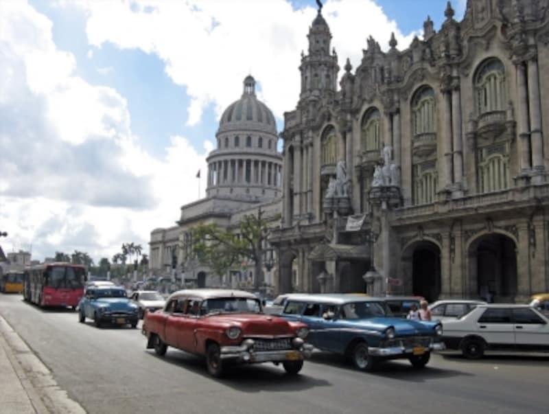 キューバの名物、アメリカ製のクラシックカーが行き交う、パセオ・デ・マルティ通り。背後の建物は手前がハバナ・アリシア・アロンソ大劇場、奥が旧国会議事堂。