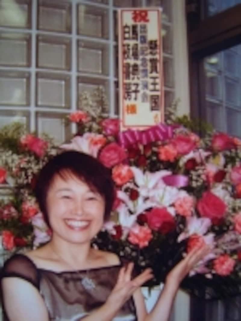 出版講演会のお祝いのお花の前にの写真で身に着けているのは当選品の100万円のプラチナダイヤペンダント