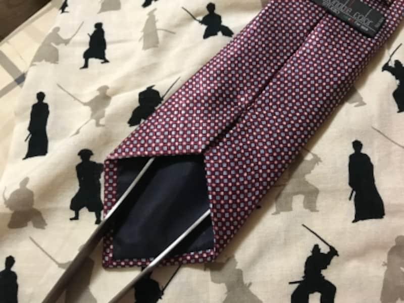 ネクタイをアイロンする際には長い棒でネクタイを膨らませる