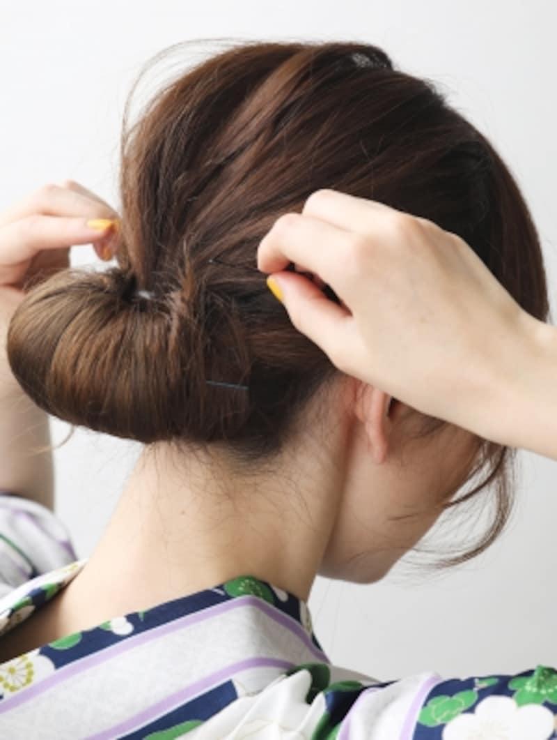 丸めた髪を左右に開いてピンで固定