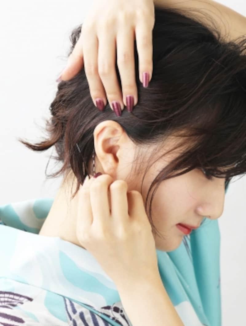 耳に髪をかけてピンで留める