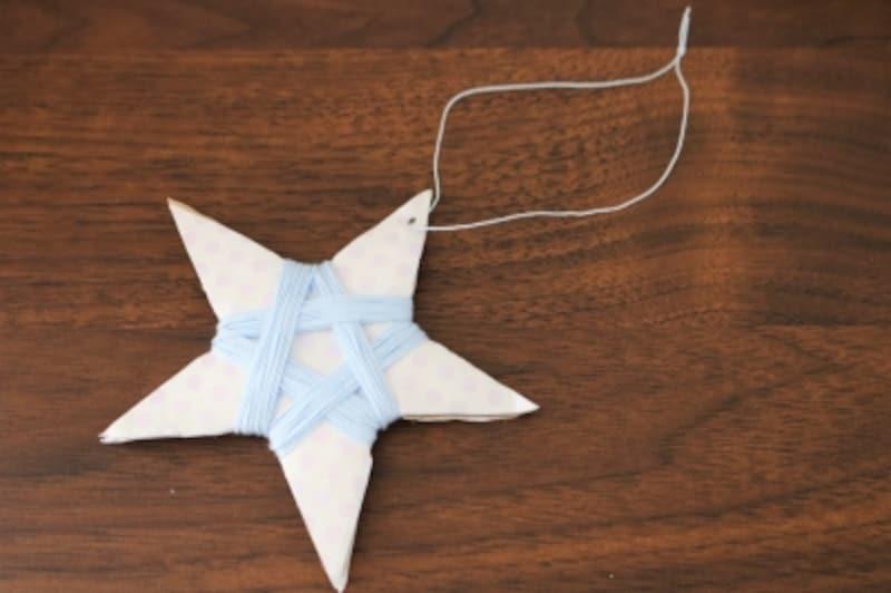 星の手作りガーランドのモチーフに穴を開け糸を通します。