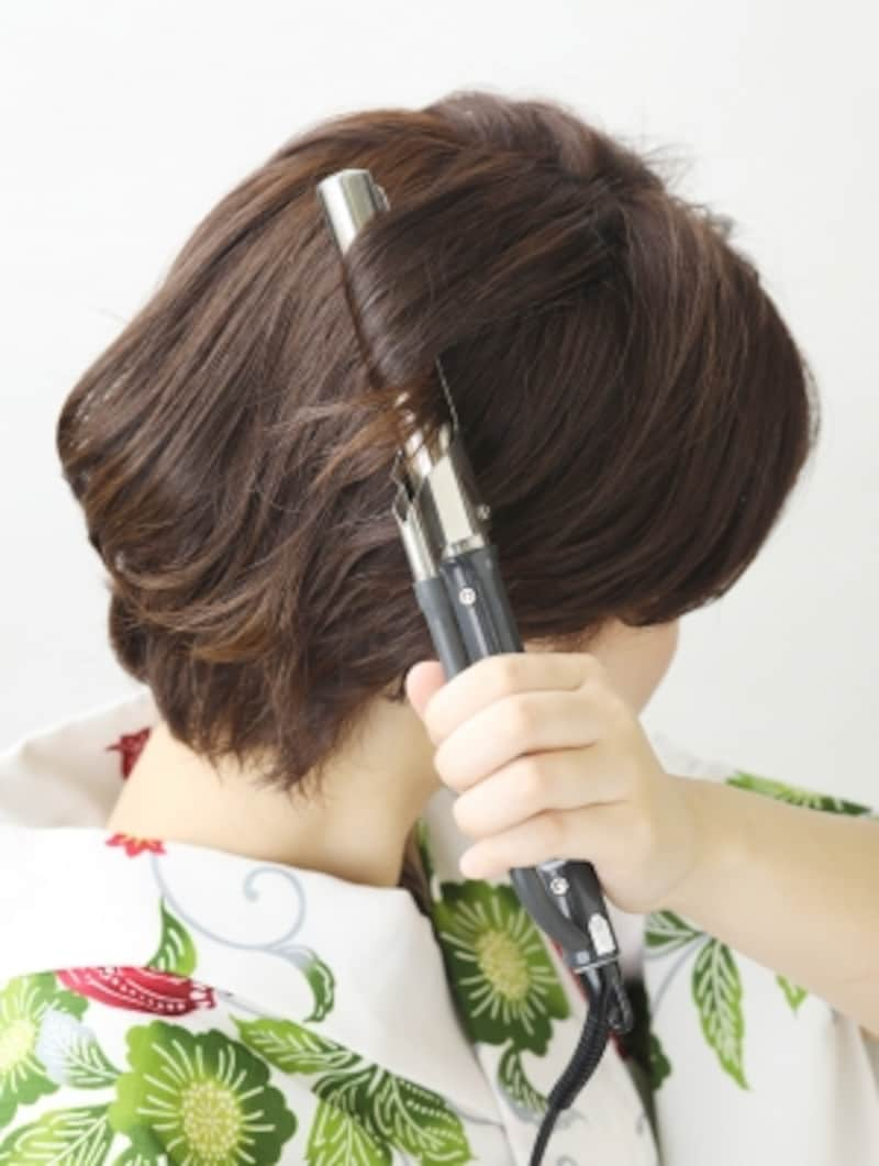 細めのコテで根元から髪を巻く