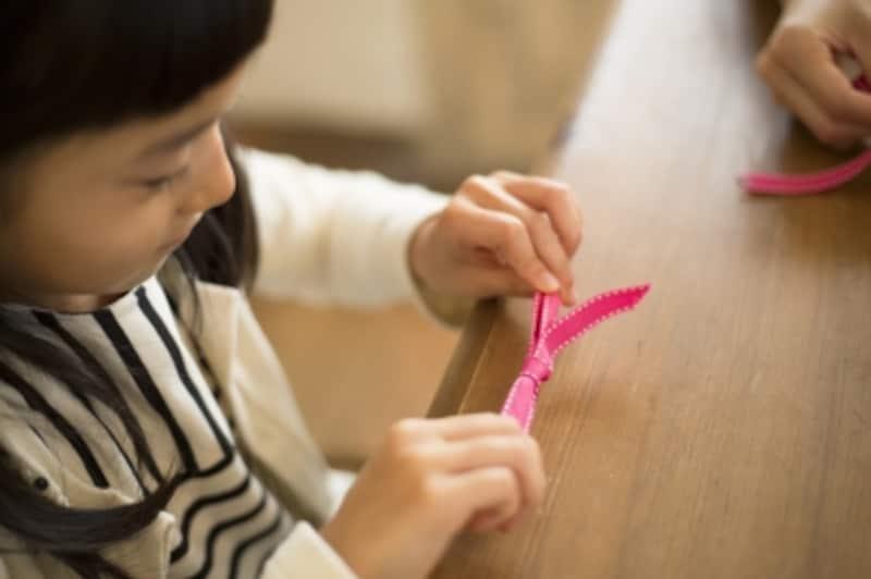 女の子がリボン結び(蝶結び)を練習している所