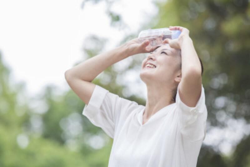 暑い屋外で水を飲む女性