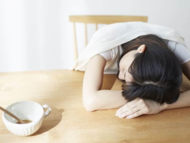 机に突っ伏して寝る女性