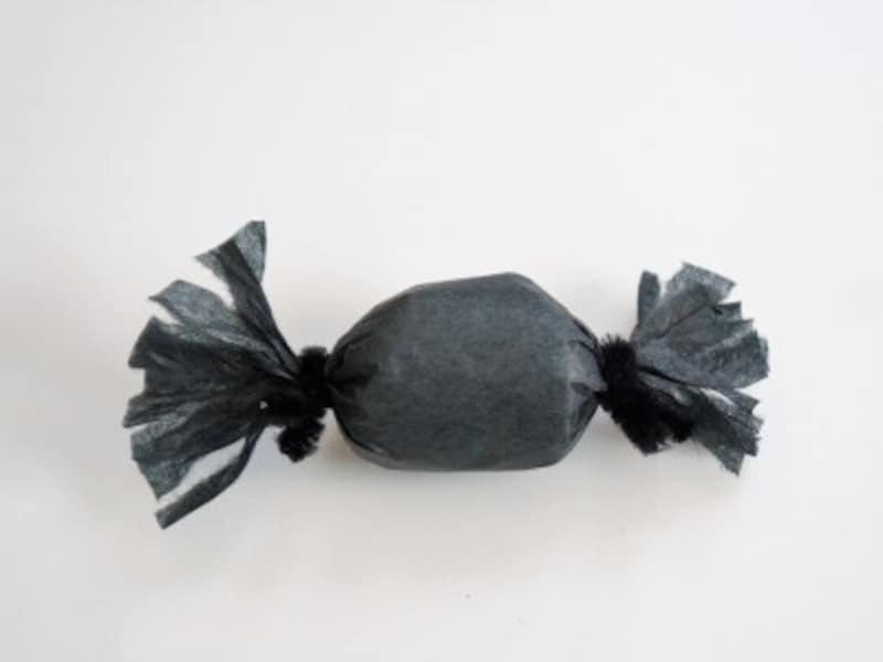 紙の両端を黒いモールでしばります。紙を少し割いてクモの足を作ります。