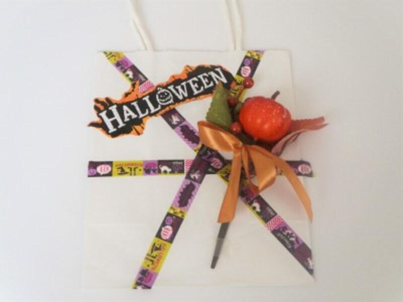 紙袋に造花やプレゼントしたい小物を透明テープでしっかりと留めます。