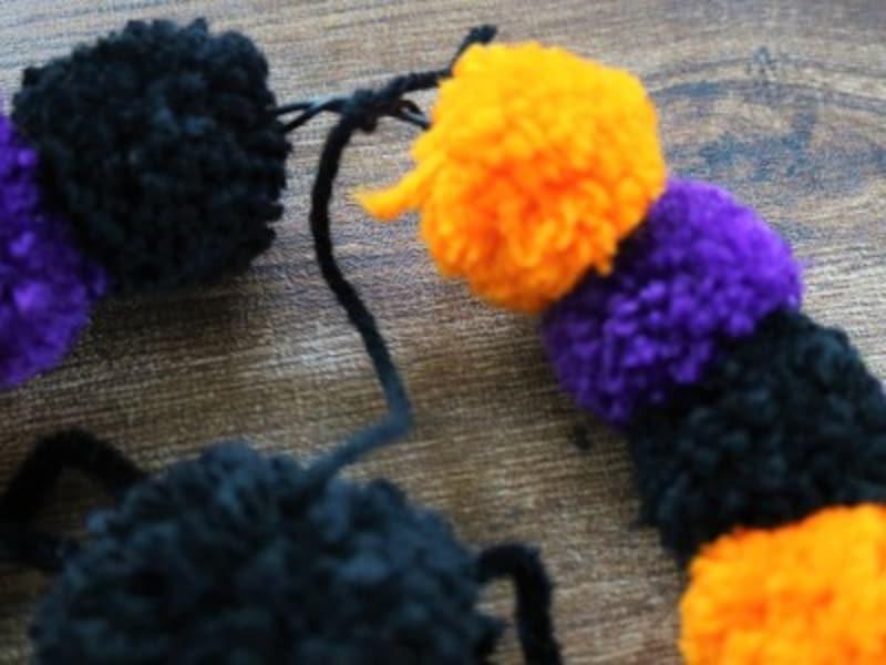 クモに結んだ毛糸の先ををリースに結び付けます。