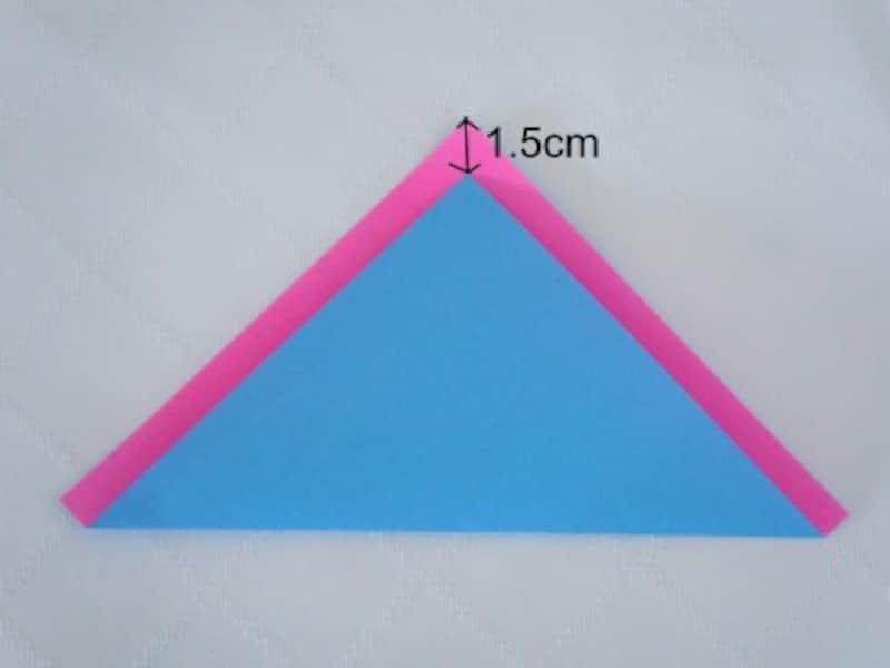 折り紙を三角に折ります。紙は少しずらして重ねます。