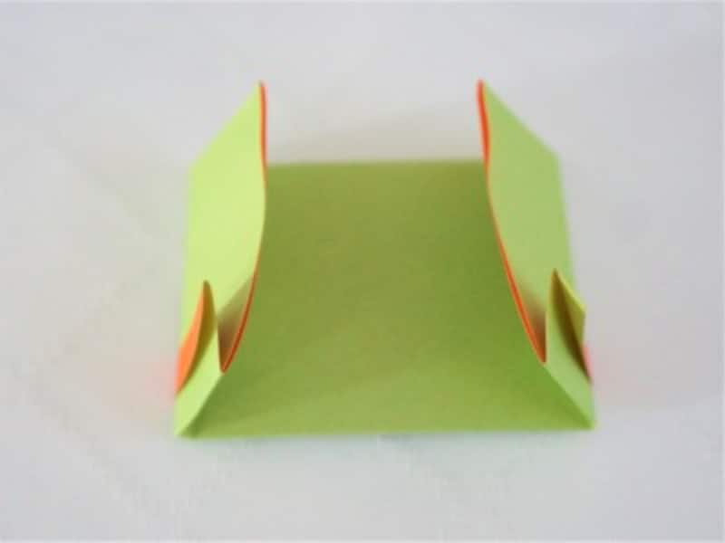 折り紙を裏返し両端を内側に折り、糊で留めます。