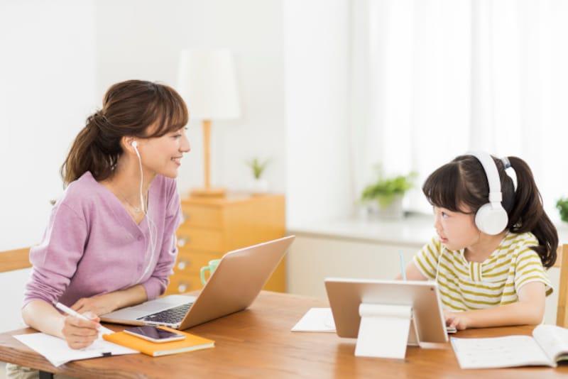 自宅でタブレット学習する子どもたち