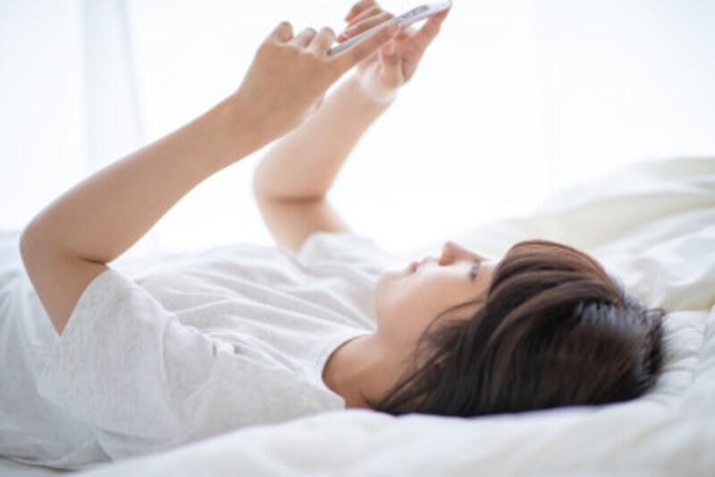 ベッドでスマホを見る女性