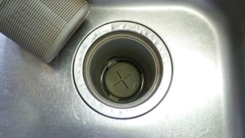排水口のストレーナーを外すと大ボス出現!その下に排水管の蓋が見えます。十の字のツマミを持って引っ張り出し、蓋の表裏を洗います。ここも臭いや詰まりの元凶です。