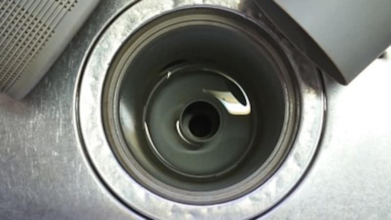 排水口ストレーナーの奥にある排水管の蓋もを外すと排水管そのものが出現!その周りや排水管の入り口も掃除を。ここまでが臭いや詰まりの元凶です。
