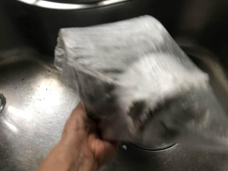 重曹を1~2カップ振りかけたら、袋を膨らませて口を閉じ、開かないようしっかり持って、振りながら全体に重曹をまぶす。