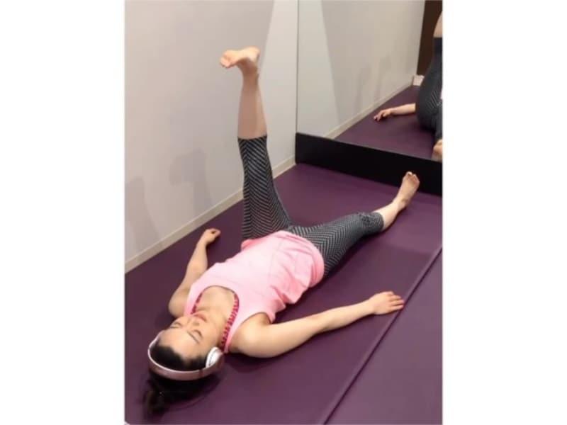 仰向けになり、片足をまっすぐ上に伸ばす