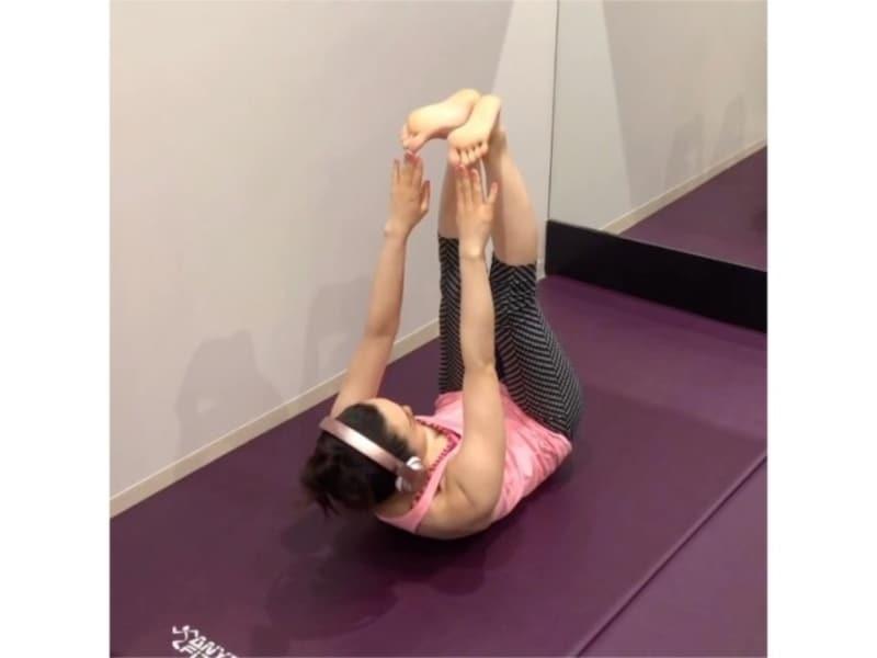 腹筋を使ってゆっくり上体をおこし、両手でつま先をタッチする