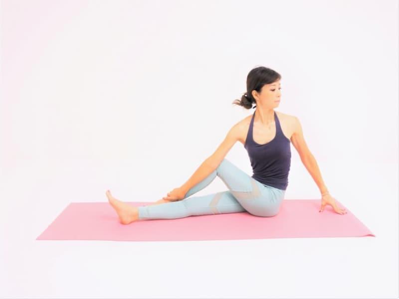 動作3:腕全体で脚を押さえ、左足首をつかみねじりを深めます